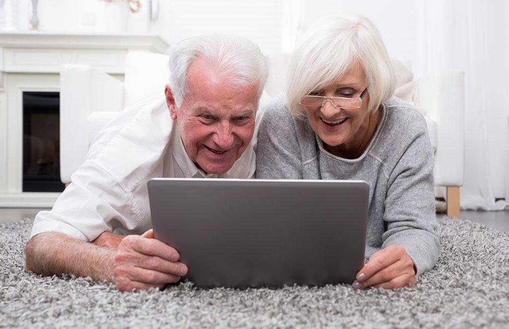 Frau und Mann gucken begeistert in einen Laptop